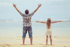 Padre e hija que juegan en la playa en el tiempo del día Fotografía de archivo