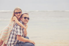 Padre e hija que juegan en la playa en el tiempo del día Foto de archivo libre de regalías