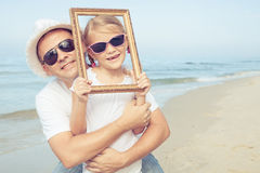 Padre e hija que juegan en la playa en el tiempo del día Fotos de archivo