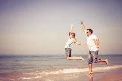 Padre e hija que juegan en la playa en el tiempo del día Fotografía de archivo libre de regalías