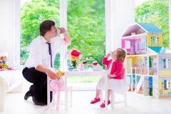 Padre e hija que juegan la fiesta del té de la muñeca Fotos de archivo libres de regalías