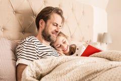 Padre e hija que leen un libro en una cama imágenes de archivo libres de regalías