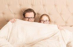 Padre e hija que ocultan debajo de un edredón en una cama fotos de archivo