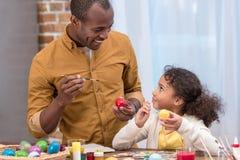 Padre e hija que pintan los huevos de Pascua y que miran uno a imagen de archivo libre de regalías