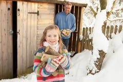 Padre e hija que recogen registros Imágenes de archivo libres de regalías