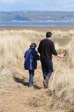 Padre e hija que recorren cerca de la costa imagenes de archivo