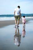 Padre e hija que recorren en la playa Fotos de archivo