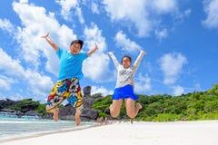 Padre e hija que saltan en la playa en Tailandia Foto de archivo libre de regalías