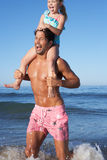 Padre e hija que se divierten en la playa Imagen de archivo libre de regalías