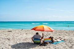 Padre e hija que se relajan debajo del paraguas anaranjado en la playa arenosa Imagen de archivo libre de regalías
