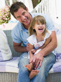 Padre e hija que se relajan en jardín Imagenes de archivo