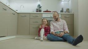 Padre e hija que se relajan en piso en cocina almacen de metraje de vídeo