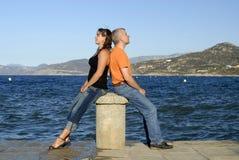 Padre e hija que se sientan delante del mar Imagen de archivo