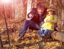 Padre e hija que se sientan en bosque y Live Nature de observación Imagenes de archivo