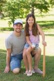 Padre e hija que sostienen el bate de béisbol en parque imagen de archivo libre de regalías
