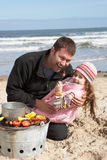 Padre e hija que tienen barbacoa en la playa Imagen de archivo