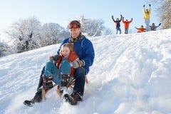 Padre e hija que tienen colina de Sledging de la diversión abajo Imagen de archivo libre de regalías