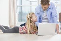 Padre e hija que usa el ordenador portátil en piso en sala de estar Imagenes de archivo