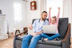 Padre e hija que usa los dispositivos Foto de archivo libre de regalías
