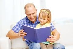 Padre e hija sonrientes con el libro en casa fotografía de archivo