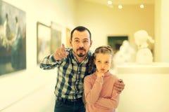 Padre e hija sorprendentes con respecto a pinturas en museo Imágenes de archivo libres de regalías