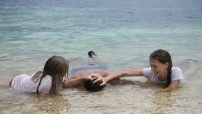 Padre e hijas que juegan en el mar metrajes