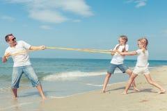 Padre e hijas que juegan en la playa en el tiempo del día Fotografía de archivo libre de regalías