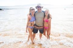 Padre e hijas que juegan junto en la playa foto de archivo libre de regalías