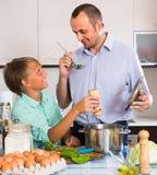 Padre e hijo adolescente que cocinan junto Foto de archivo libre de regalías