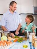 Padre e hijo adolescente que cocinan junto Imagenes de archivo