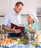 Padre e hijo adolescente que cocinan junto Imágenes de archivo libres de regalías