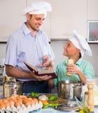 Padre e hijo adolescente que cocinan junto Foto de archivo