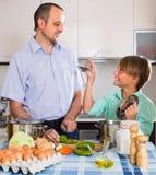 Padre e hijo adolescente que cocinan junto Imagen de archivo libre de regalías