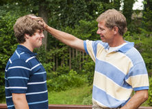 Padre e hijo adolescente que son juguetones, divirtiéndose junto Imágenes de archivo libres de regalías