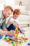 Padre e hijo adorable que juegan con el constructor en piso en casa Foto de archivo libre de regalías