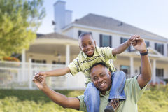 Padre e hijo afroamericanos juguetones delante del hogar Fotos de archivo libres de regalías