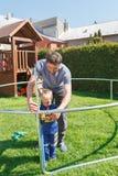 Padre e hijo al instalar los trampolines grandes del jardín Imagen de archivo libre de regalías
