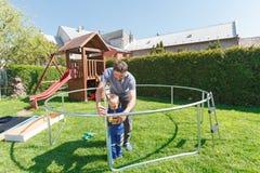 Padre e hijo al instalar los trampolines grandes del jardín Imagen de archivo