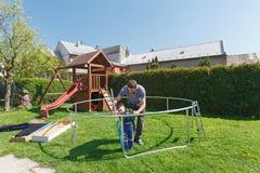 Padre e hijo al instalar los trampolines grandes del jardín Foto de archivo