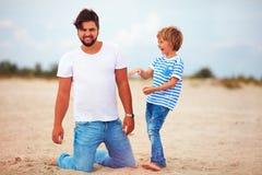 Padre e hijo alegres, familia que se divierte, jugando en la playa del verano Fotos de archivo
