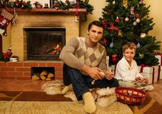 Padre e hijo cerca de la chimenea en casa de la Navidad Fotos de archivo libres de regalías