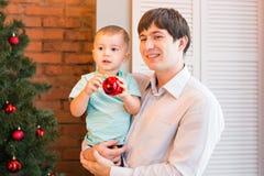 Padre e hijo cerca del árbol de navidad en el cuarto Imagen de archivo libre de regalías
