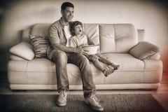 Padre e hijo con el cuenco de las palomitas que ven la TV en la sala de estar foto de archivo