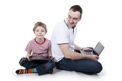 Padre e hijo con el ordenador. Imágenes de archivo libres de regalías