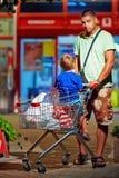 Padre e hijo con la carretilla después de hacer compras Fotos de archivo libres de regalías