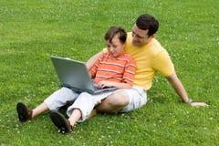 Padre e hijo con la computadora portátil Imagen de archivo libre de regalías