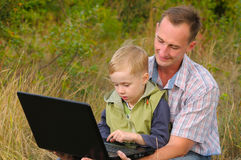 Padre e hijo con la computadora portátil Foto de archivo libre de regalías