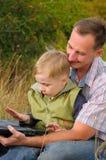 Padre e hijo con la computadora portátil Fotografía de archivo libre de regalías