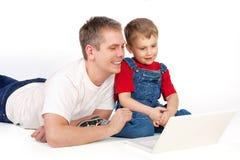 Padre e hijo con la computadora portátil Fotos de archivo