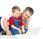 Padre e hijo con la computadora portátil Fotos de archivo libres de regalías